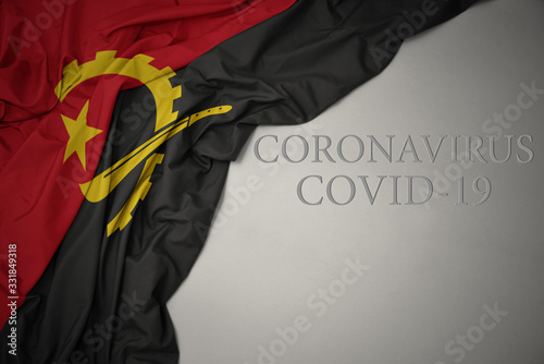Photo waving national flag of angola on a gray background with text coronavirus covid-19