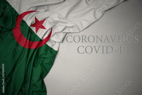 Photo waving national flag of algeria on a gray background with text coronavirus covid-19