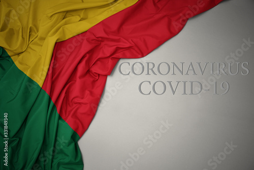 Photo waving national flag of benin on a gray background with text coronavirus covid-19