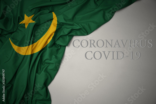 Cuadros en Lienzo waving national flag of mauritania on a gray background with text coronavirus covid-19