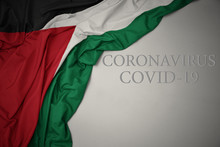 Waving National Flag Of Palestine On A Gray Background With Text Coronavirus Covid-19 . Concept.