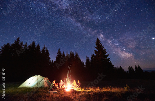 Fotografía Night camping near bright fire in spruce forest under starry magical sky with milky way