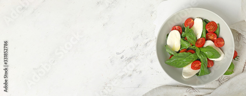 Fototapeta Mozzarella cheese with tomatoes and basil on white background with space for text obraz