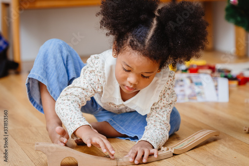 Fotomural little cute child girl enjoy playing wood puzzle on the wooden floor at home in living room