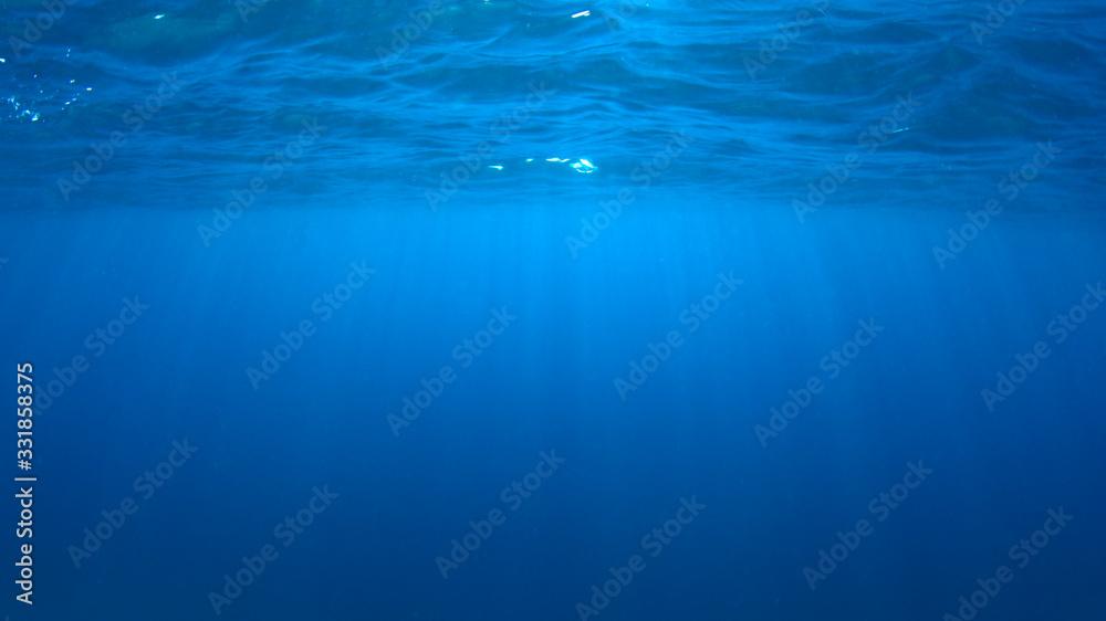 Fototapeta Underwater blue background photo of ocean surface and sunlight