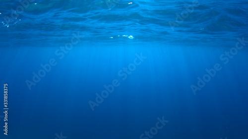 Obraz Underwater blue background photo of ocean surface and sunlight - fototapety do salonu