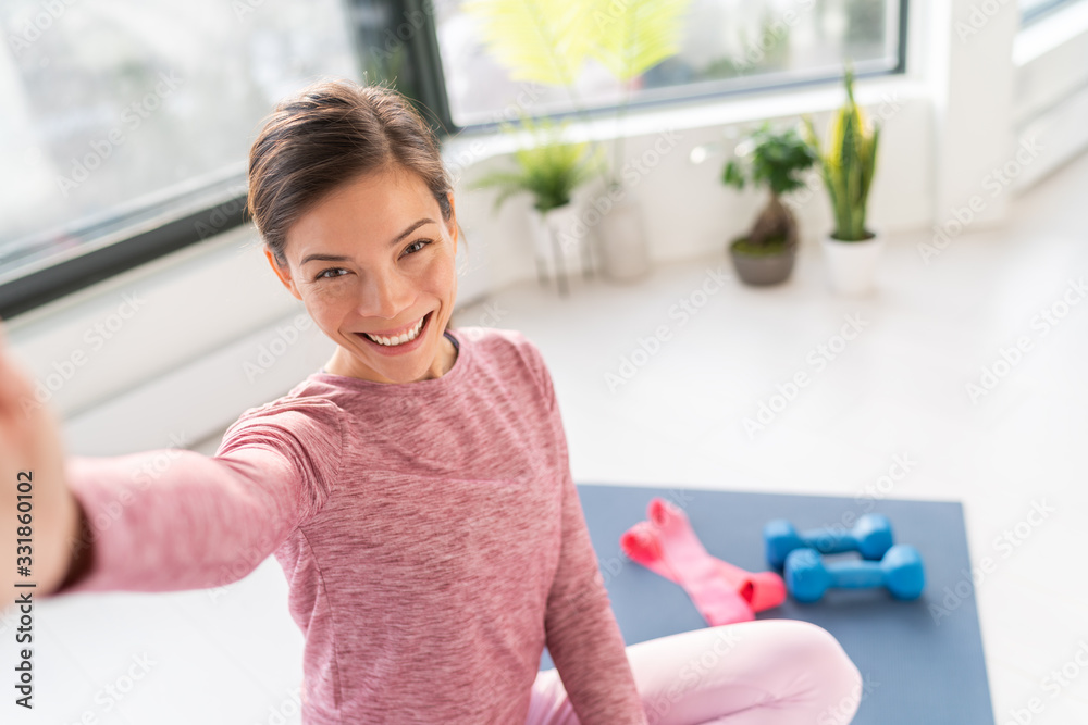 Fototapeta Happy selfie at home Asian young woman smiling training bodyweight exercises on exercise mat in living room of apartment taking mobile phone photo during workout.