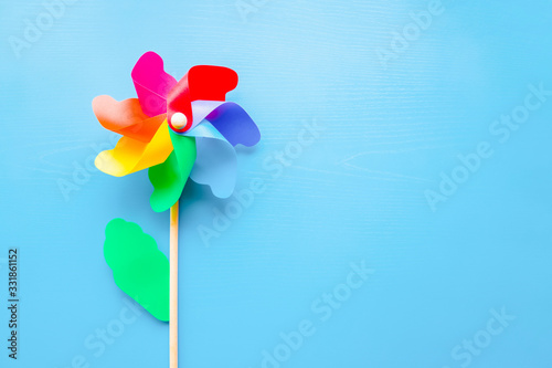 Cuadros en Lienzo Colorful plastic toy windmill propeller flower for kids on blue background