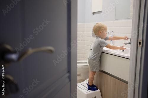 Fotografija Little blond boy learning brushing his teeth in bath