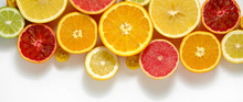 Close Up Image Of Juicy Organic Whole And Halved Assorted Citrus Fruits With Visible Core Texture, Isolated White Background, Copy Space. Vitamin C Loaded Food Concept. Top View, Flat Lay.
