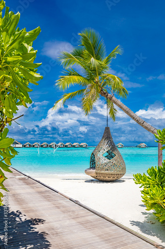 Tropical beach background as summer landscape with beach swing or hammock and white sand and calm sea for beach banner Fototapeta