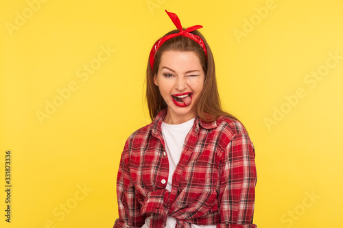 Portrait of optimistic pinup girl in checkered shirt and headband winking to cam Wallpaper Mural