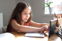 Caucasian Preteen Girl Concentrated On Her Task With Tablet. Concept Of Distance Learning In Isolation
