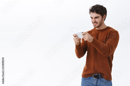 Guy having intense fight in shooter game, holding mobile phone and grimace from Canvas Print