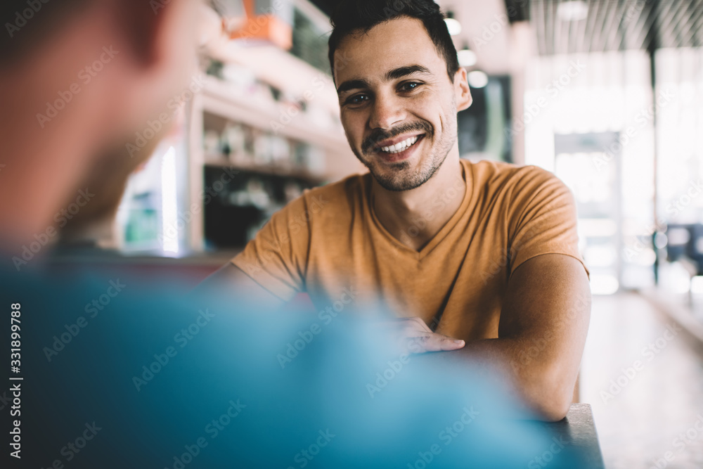 Fototapeta Cheerful young male friends having meeting in cafe