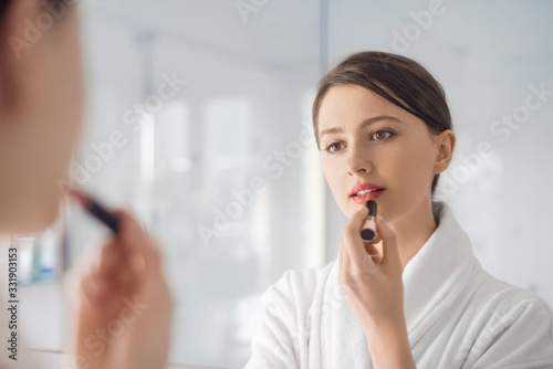 Fotografiet A young woman putting on lipstick