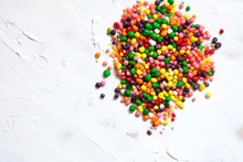 Rainbow Colored Candy Sprinkled On A White Background