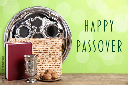 Obraz Symbolic Pesach (Passover Seder) items on wooden table against green background - fototapety do salonu