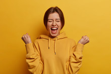 Lucky Positive Woman Feels Happy And Relieved, Achieves Reward, Clenches Fists With Triumph, Celebrates Great Amazing News, Exclaims With Joy, Wears Casual Hoodie, Isolated On Yellow Background