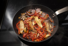 Steaming Cooking Pan With Roasting Vegetables Like King Oyster Mushrooms, Red Peppers And Onions On A Black Stove, Copy Space