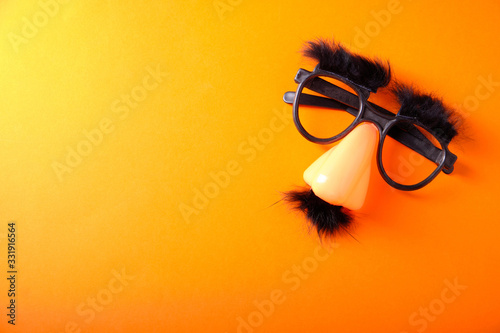 Photo Overhead glasses, nose and mustache for April 1, April Fool's Day, on orange bac