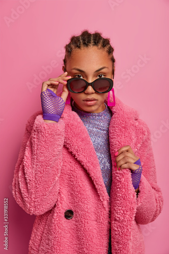 Self assured stylish woman looks from sunglasses, wears luxurious warm coat, has own style, follows fashion trends, poses indoor against pink background. Serious Afro American lady in fashion attire - 331918552