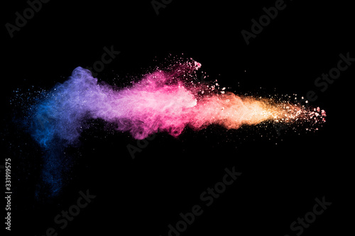 Colorful background of pastel powder explosion.Rainbow color dust splash on black background.