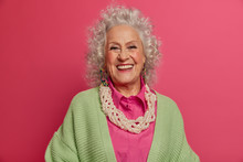 Headshot Of Good Looking Elderly Woman Smiles Broadly, Makes Photo For Long Memory, Being In Happy Mood, Dressed In Elegant Clothes, Isolated On Pink Background. Beauty, Style, Age, Fashion Concept