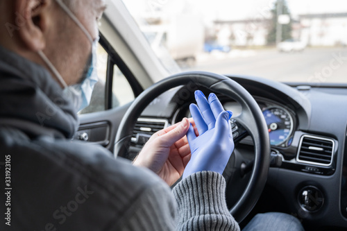 Vászonkép Man in the medical mask puts on rubber gloves for protect himself from bacteria and virus while driving a car