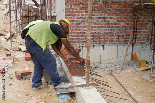 Fototapety, obrazy: Brickwork by construction workers at the construction site. Workers laying the clay brick and stacked it together using mortar to form the wall.