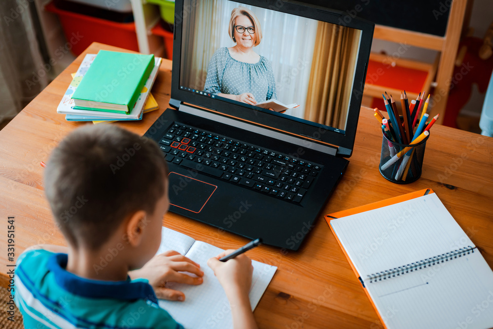 Fototapeta Distance learning online education. A schoolboy boy studies at home and does school homework. A home distance learning