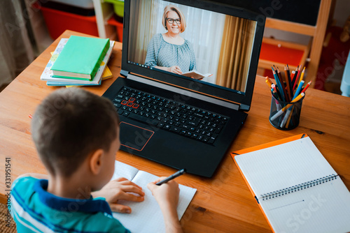 Distance learning online education. A schoolboy boy studies at home and does school homework. A home distance learning - 331951541