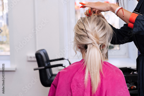 hands of a professional hairdresser make a low bun hairstyle for a blonde girl