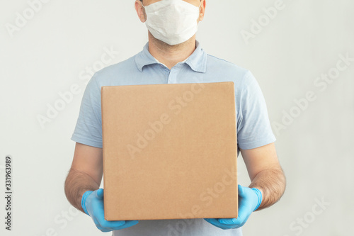Vászonkép Delivery man holding cardboard boxes in medical rubber gloves and mask