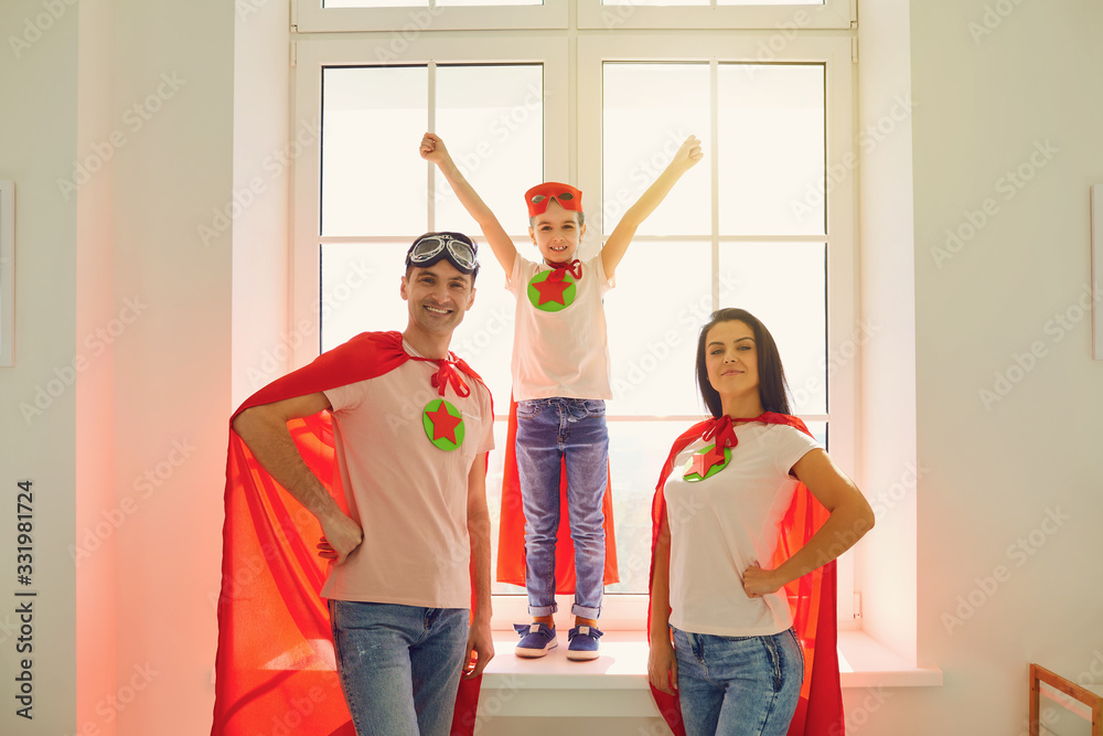 Fototapeta Happy cheerful family in costumes of super heroes laughing while standing against the background of a window in a room indoors.