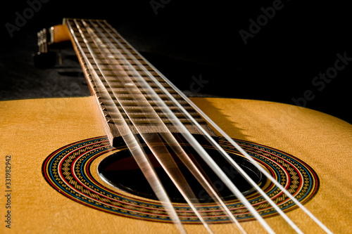 Leinwand Poster Classical guitar with vibrating strings on a black   background