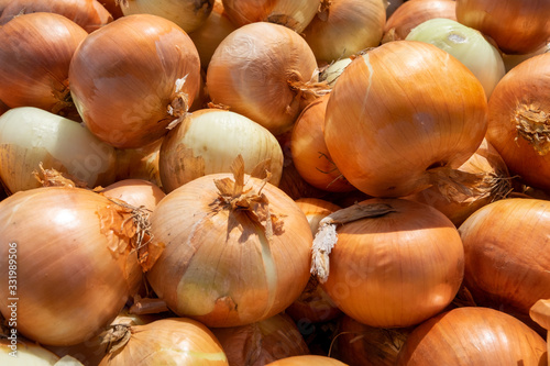 Photo A large bunch of unpeeled raw yellow onions