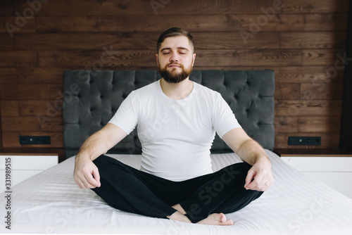 Stampa su Tela Handsome caucasian man meditating and mindful on his bed in bedroom