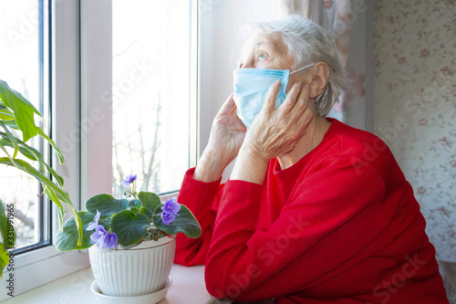 The Covid-19, health, safety and pandemic concept - senior old lonely woman sitting near the window