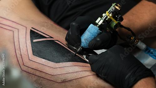 Photo Professional tattoo artist makes tattoo on man leg