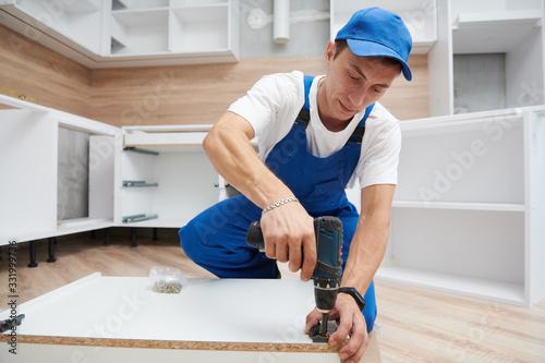 kitchen installation. Worker assembling furniture Wallpaper Mural
