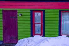The Exterior Wall Of A Brightly Colored House With Lime Green Clapboard, A Purple Wooden Door And Pink Trim Double Hung Windows. There's A Mound Of White Snow In Front Of The Building.