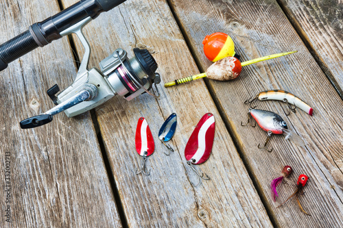 fishing rod, reel, lures, and bobbers on a wooden background Fototapet