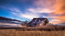 Old Rural Farmhouse In The Countryside During A Very Colorful Sunset. There Is A Grass Meadow And A Few Trees.
