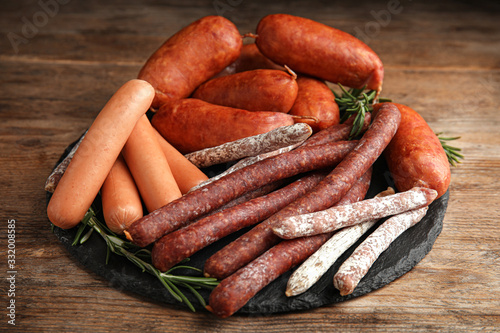 Different tasty sausages served on wooden table Wallpaper Mural