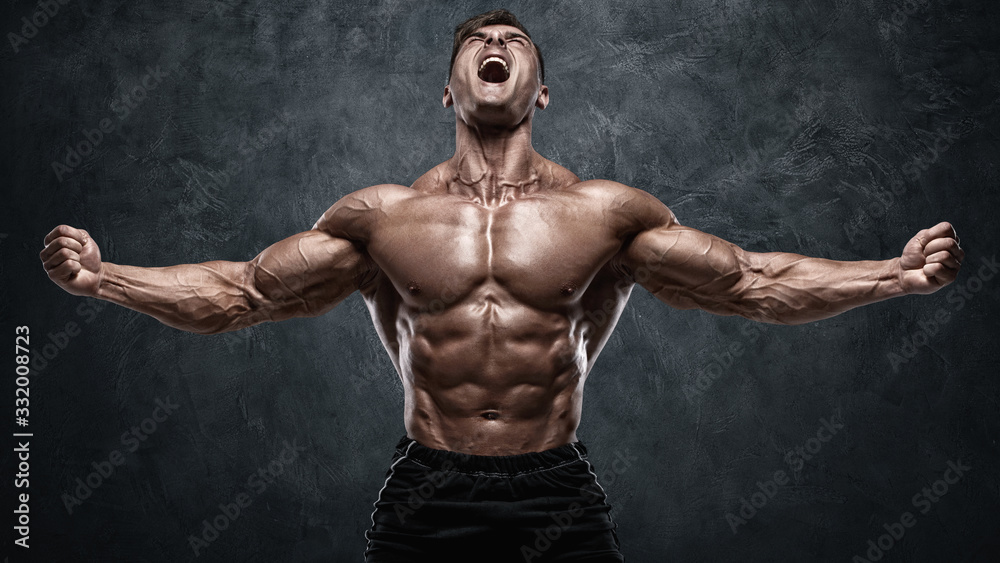 Fototapeta Muscular man showing muscles on wall background. Strong male naked torso abs
