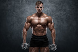 Muscular man with dumbbells on wall background. Strong male naked torso abs