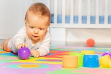Baby Toddler Boy Creep On The Floor Of Nursery Grabbing Colorful Ball