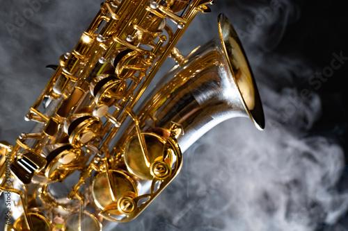 Obraz Golden shiny alto saxophone on black background with smoke. copy space - fototapety do salonu