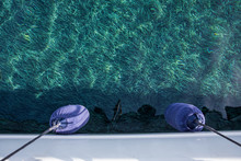 Crystal Clear Water With Seaweeds On The Sea Bottom And Two Blue Fenders To Protect The Hull Of The Yacht Off The Coast Of Kastos Island, Ionian Sea, Greece In Summer.